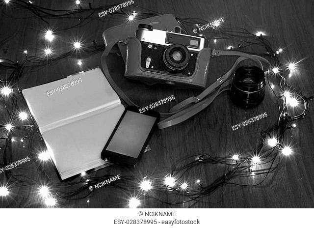 the old camera on a table with New Year fires and a photo album