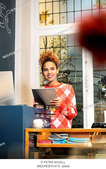 Young woman working in fashion store, using ldigital tablet