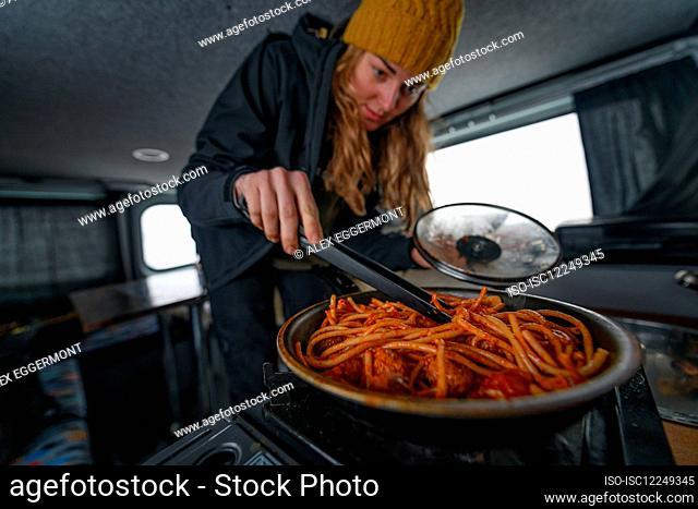 A woman in a campervan stirring food in a saucepan wearing a woolly hat. Winter road trip