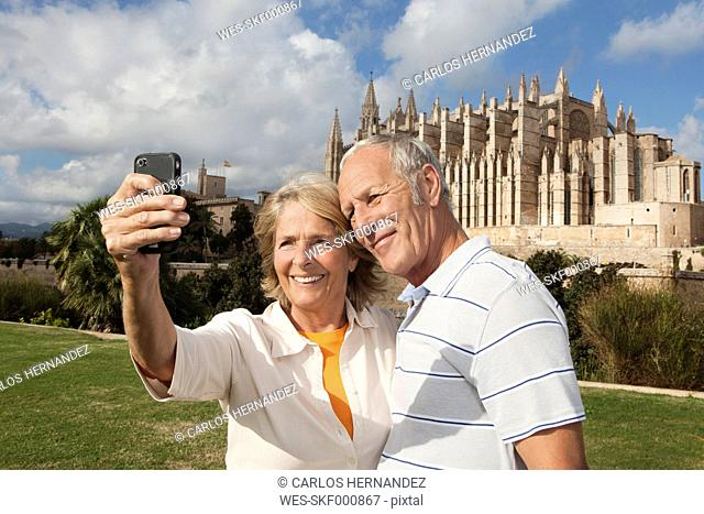 Spain, Mallorca, Palma, Senior couple smiling taking picture with Cathedral Santa Maria, portrait
