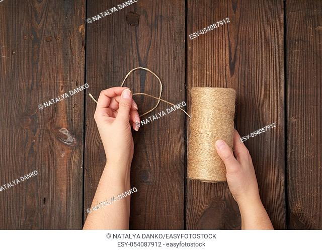 female hands holding a skein with brown eco thread on a brown wooden background, top view