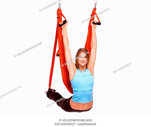 Young woman upside down doing anti-gravity aerial yoga in hammock on a white background