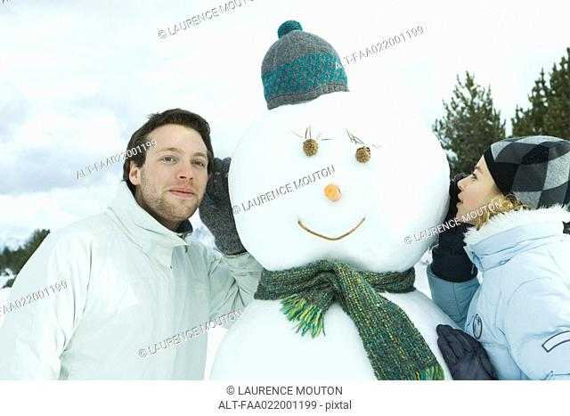 Brother and sister leaning against snowman, sister whispering, brother listening