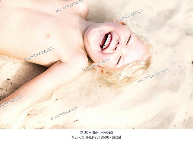 Happy girl lying on sand