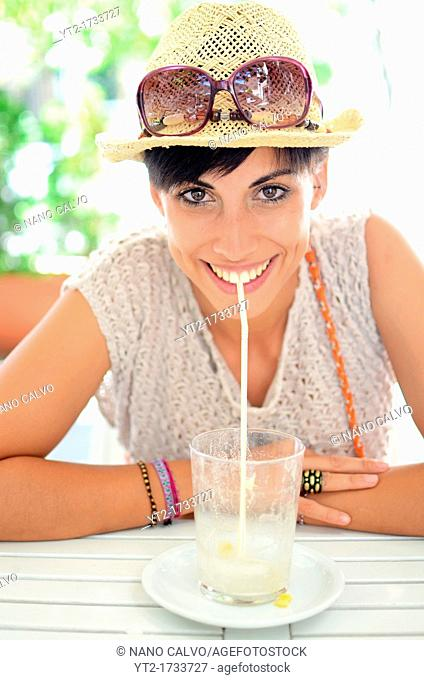 Attractive young woman with summer style drinks a juice in cafeteria
