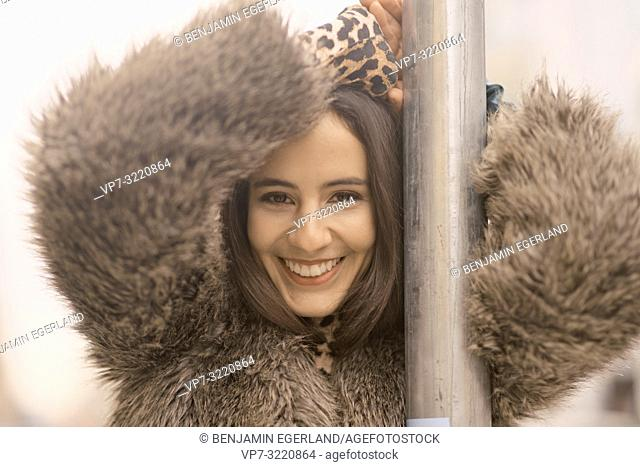 portrait of young woman in winter coat leaning on traffic sign at street in city, happy smiling, in Munich, Germany