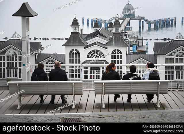 09 May 2020, Mecklenburg-Western Pomerania, Sellin: Tourists sit on a bench on the beach promenade in front of the pier in the Baltic resort Sellin