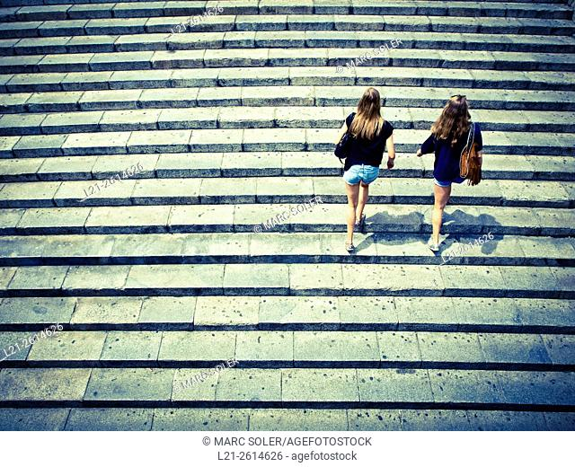 Two young women climbing stairs during a summer day. Barcelona, Catalonia, Spain