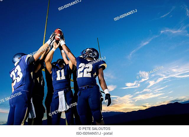 Teenage and young male american football team celebrating and holding up ball