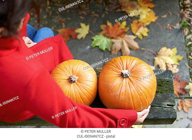 High angle view of mature woman with arm around two pumpkins on garden bench
