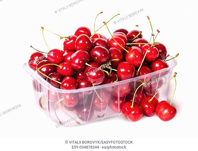 Sweet cherries in plastic tray and three near top view isolated on white background