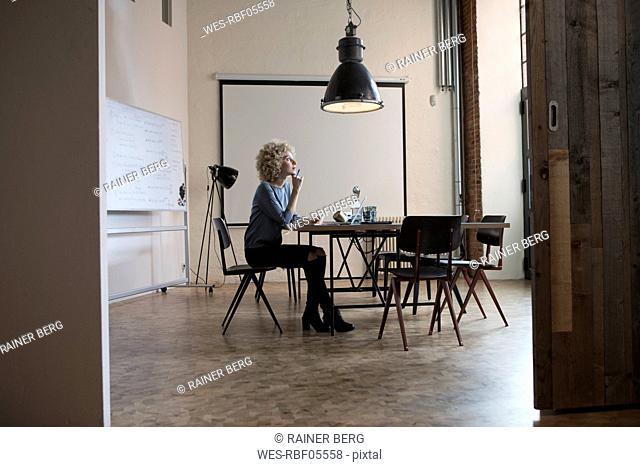 Woman in boardroom thinking