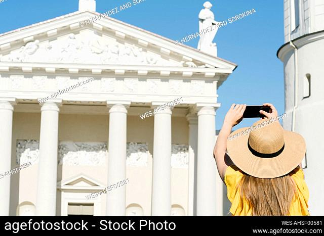 Rear view of woman photographing cathedral with smart phone in city during sunny day