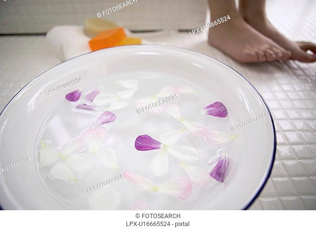 Young woman standing by bowl of water with flower petals, close up