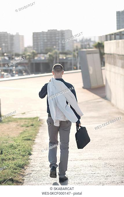 Back view of walking businessman carrying jacket and bag