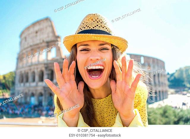 Happy young woman shouting through megaphone shaped hands in fro