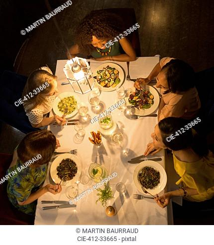 Women friends talking and dining at restaurant table