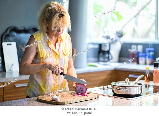 A mature woman is slicing red onion rings on a cutting board in order to prepare a meal