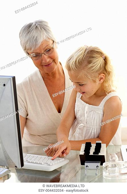 Granddaughter explaining her grandmother how to use a computer