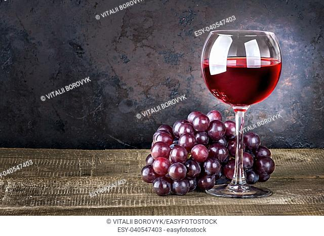 Wineglass with red wine and red grapes on wooden table. Dark background