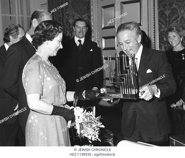 Greville Janner presents the Queen with a menorah at the Jewish Commonwealth Leaders Conference, December 1982. Greville Janner (born 1928) was President of the...
