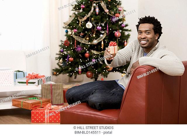 Smiling Black man holding Christmas gift in living room