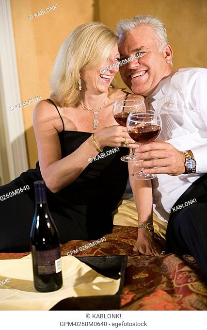 Romantic mature couple in formal attire with wine in bedroom