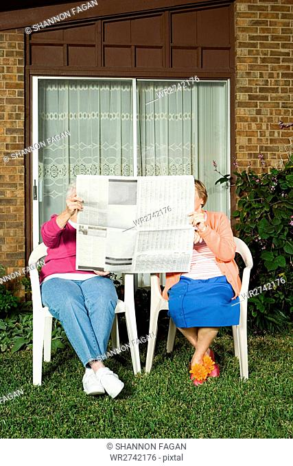 Two senior women sharing a newspaper