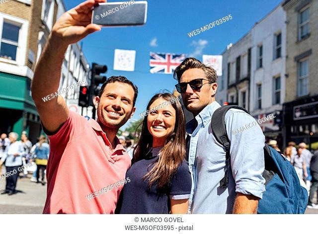 UK, London, Portobello Road, portrait of three friends taking selfie with smartphone
