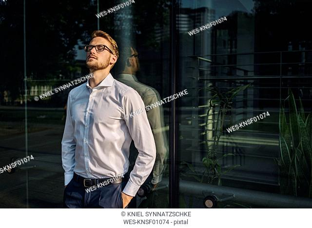 Businessman leaning against glass wall