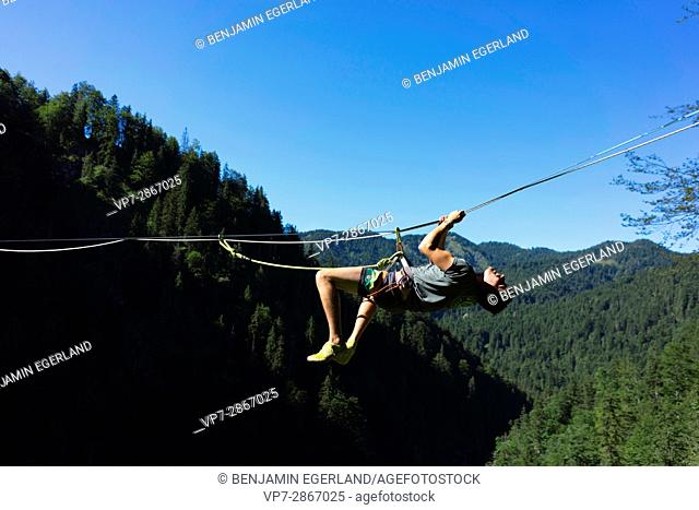 young outdoor sportsman climbing on highline slackline over valley in south of Germany, Bavaria, near border to Austria