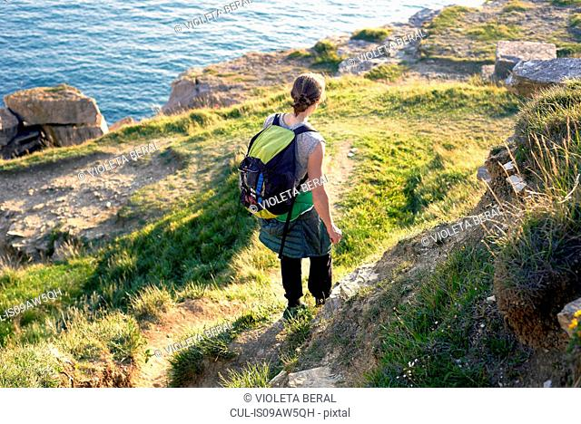 High angle rear view of hiker with backpack hiking down cliff side, Portland, UK