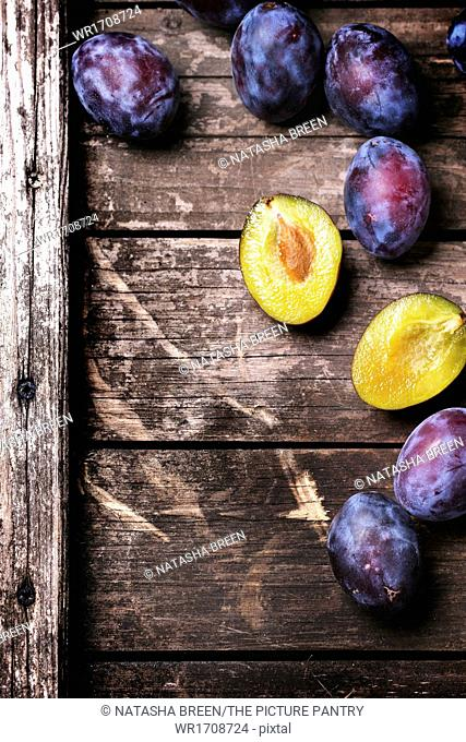 Whole and sliced plums over old wooden table