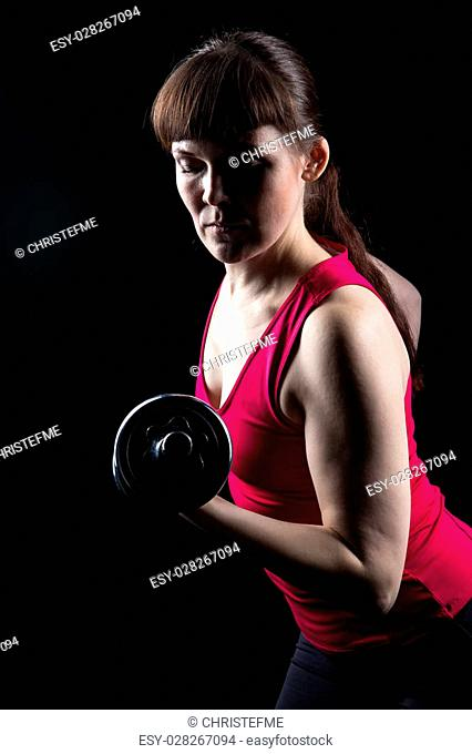 Serious trainer with kettlebell on black background