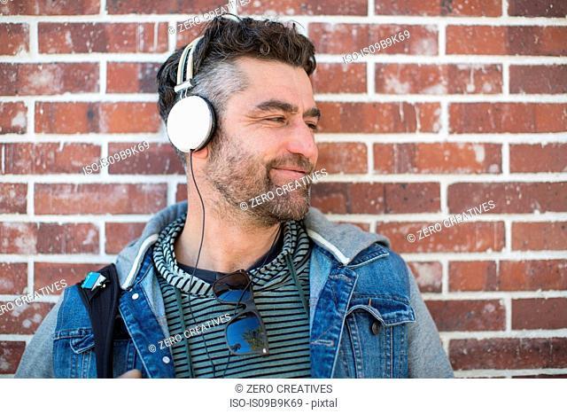 Mid adult man leaning against wall, wearing headphones, looking away, smiling