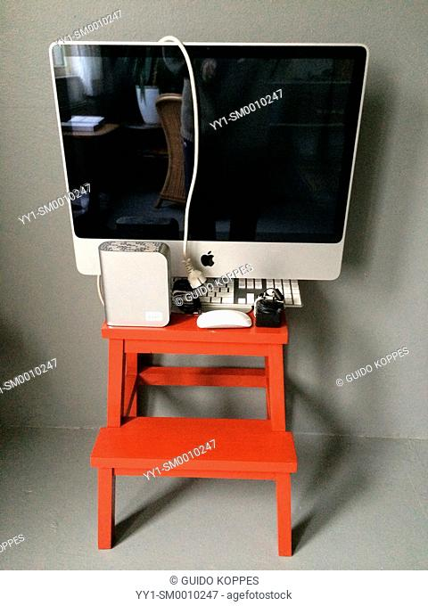 Studio Tuinstraat, Tilburg, Netherlands. Red stool with depreciated iMac desktop computer and external hard drive, ready for sale as second hand equipment