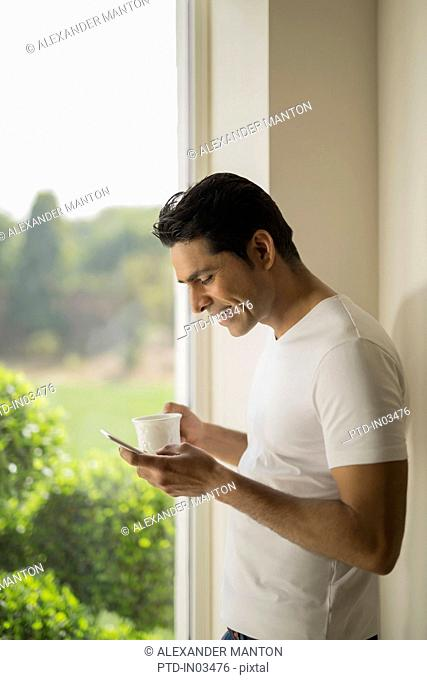 India, Man at window holding coffee cup and mobile phone