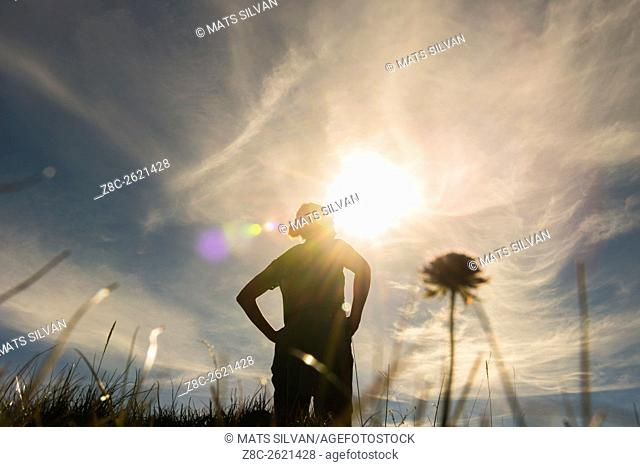 Low angle view on a proud woman in backlit with sunshine and grass and flower in Grisons, Switzerland