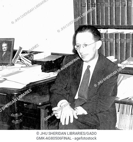 Candid portrait of Nathan Edelman, Chairman of the Department of Romance Languages at Johns Hopkins University, sitting in his office in front of bookshelves