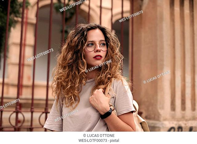 Beautiful young woman with curly hair and glasses in the city