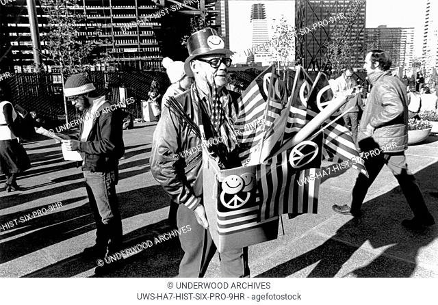 San Francisco, California: c. 1968 A man with smiley face buttons and American flags with the peace symbol during an anti Vietnam war demonstration