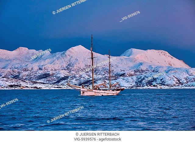 NORWAY, HANSNES, 01.11.2017, sunrise over fjord with winter landscape and sailship near Tromso, Troms, northern Norway, Europe - Hansnes, Troms, Norway