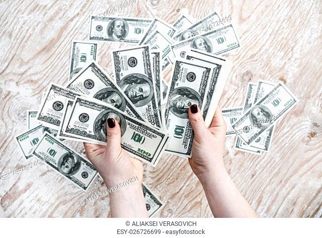 Dollars in hands. Cash in hands. Fake money in hands. Money in female hands on light wooden background