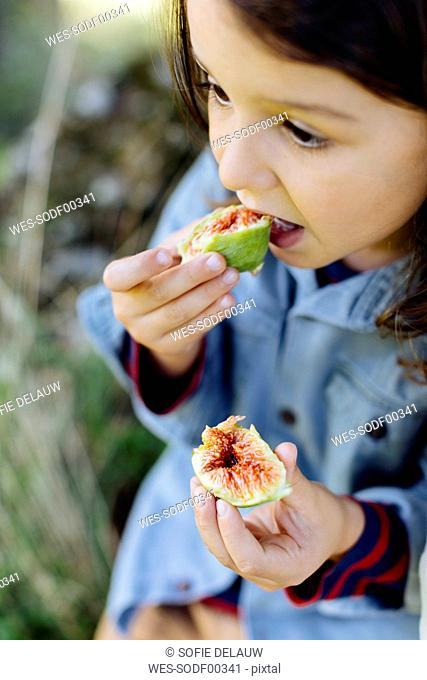 Child eating a fig outdoors