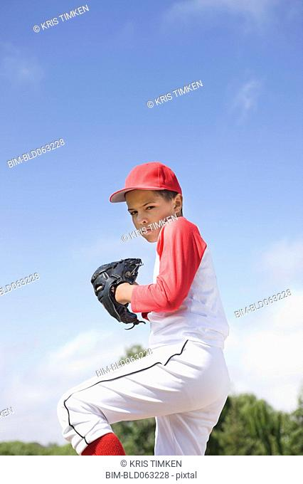 Mixed race boy in baseball uniform pitching in game