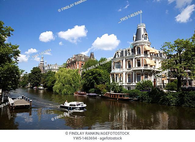 Small motor boat on the Singel Gracht Canal near Marie Heineken Plein, Amsterdam, Holland, Northern Netherlands