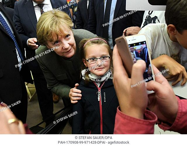 German Chancellor Angela Merkel poses for a picture with a young boy during a CDU election campaign event in Wolgast, Germany, 08 September 2017