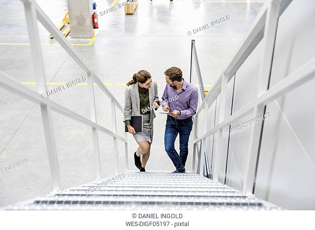 Colleagues in company talking on stairs