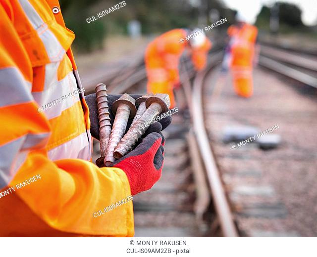 Railway maintenance worker holding track screws, close up