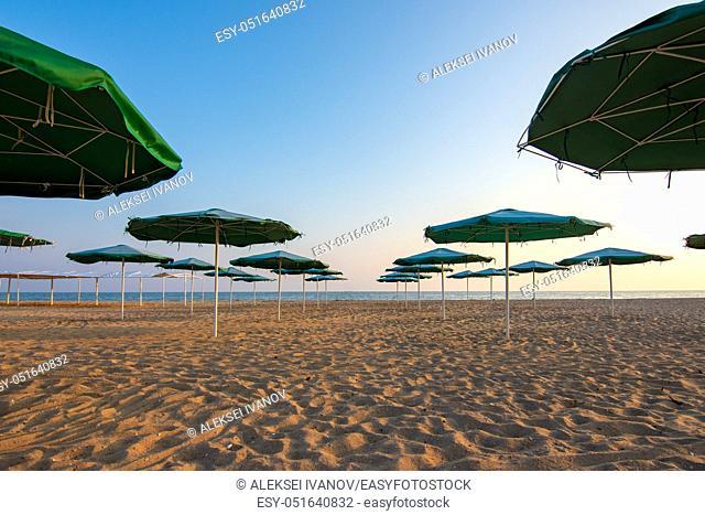 Opened umbrellas on a deserted evening sandy beach